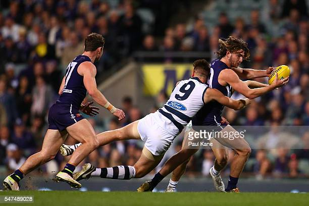 Connor Blakely of the Dockers gets tackled by Zac Smith of the Cats during the round 17 AFL match between the Fremantle Dockers and the Geelong Cats...