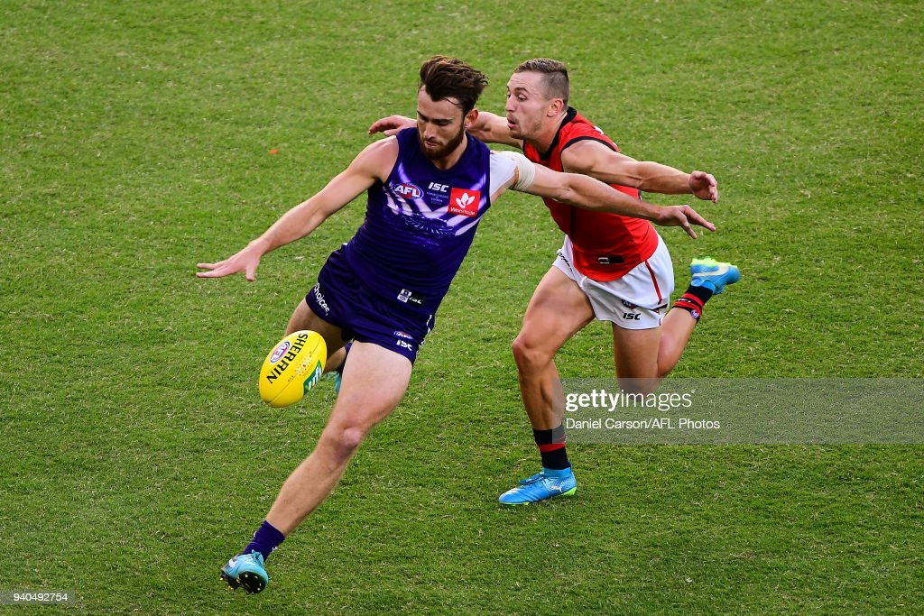 Connor Blakely of the Dockers is pressured on a kick by Devon Smith of the Bombers during the 2018 AFL round 02 match between the Fremantle Dockers and the Essendon Bombers at Optus Stadium on March 31, 2018 in Perth, Australia.