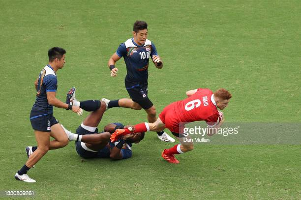 Connor Braid of Team Canada is tackled by Lote Tuqiri of Team Japan during the Men's Pool B Rugby Sevens match between Canada and Japan on day four...