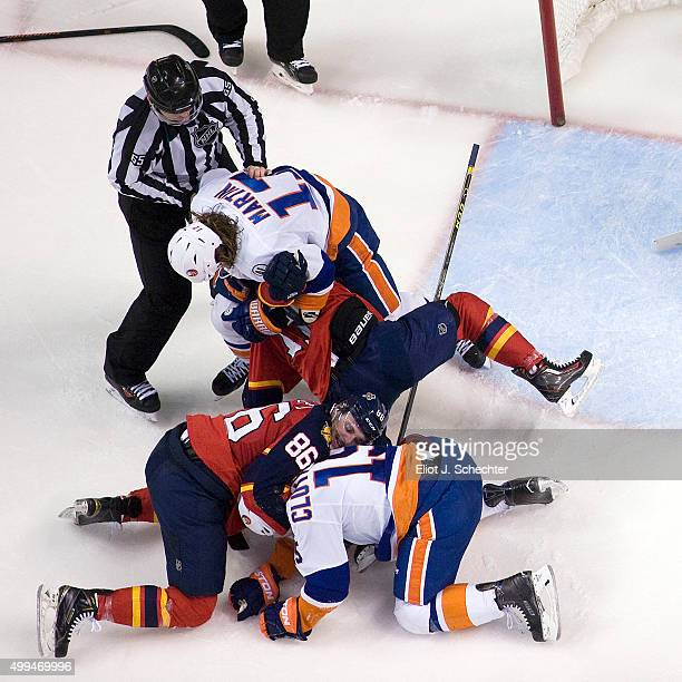 Connor Brickley of the Florida Panthers and teammate Derek MacKenzie fight with Cal Clutterbuck of the New York Islanders and teammate Matt Martin at...