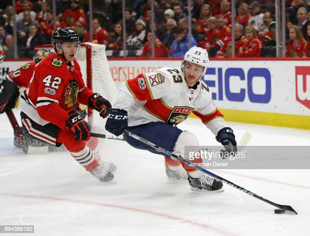 Connor Brickley of the Florida Panthers looks to pass next to Gustav Forsling of the Chicago Blackhawks at the United Center on December 12 2017 in...