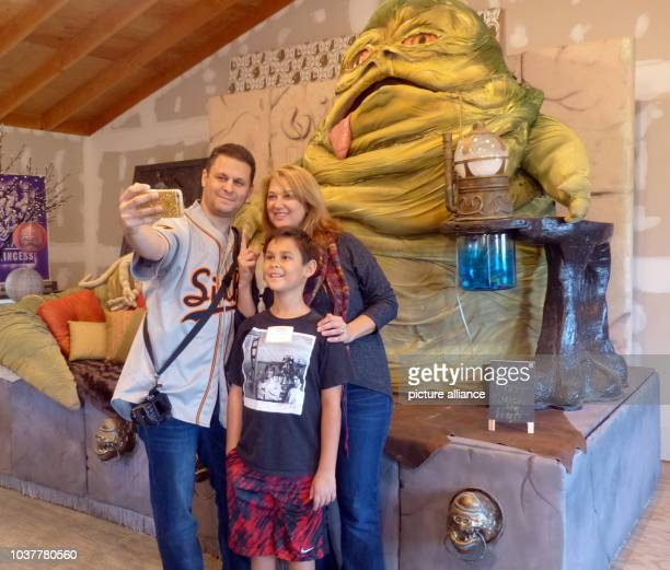 Connor Brooks and his parents Amy and Craig Brooks from Walnut Creek California take a selfie in front of a Jabba the Hutt statue at the Obi Wan...
