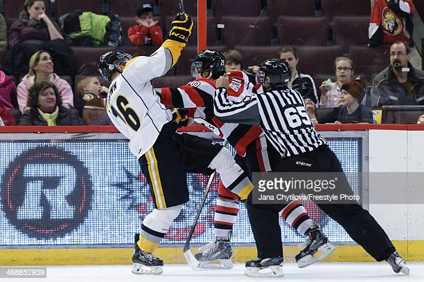 Connor Brown of the Ottawa 67's shoves Davis Brown of the Sarnia Sting as linesman Scott Wilson tries to separate tham during an OHL game at Canadian...