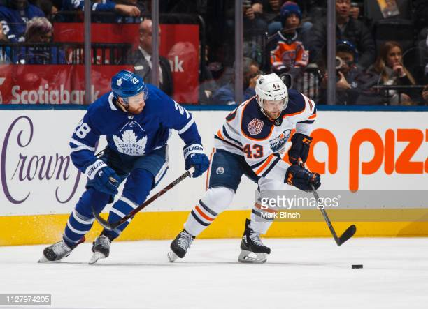 Connor Brown of the Toronto Maple Leafs battles for the puck against Josh Currie of the Edmonton Oilers during the first period at the Scotiabank...