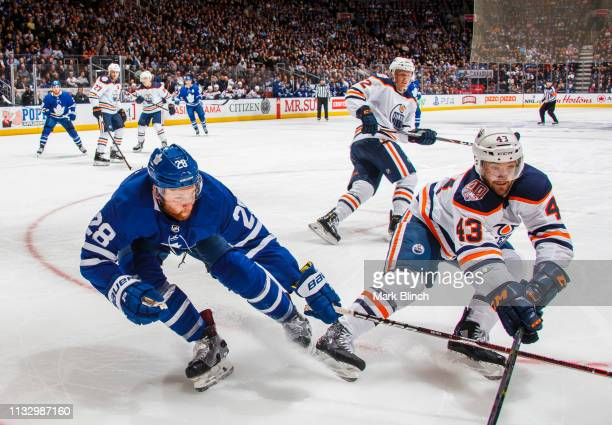 Connor Brown of the Toronto Maple Leafs battles with Josh Currie of the Edmonton Oilers during the third period at the Scotiabank Arena on February...