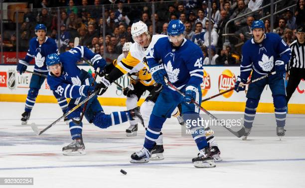 Connor Brown of the Toronto Maple Leafs shoots at an empty net beside teammate Nazem Kadri against Evgeni Malkin of the Pittsburgh Penguins during...