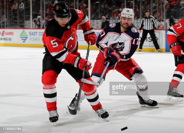 Connor Carrick of the New Jersey Devils tries to take a shot as Brandon Dubinsky of the Columbus Blue Jackets defends on March 05 2019 at Prudential...