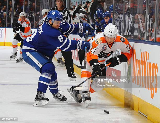Connor Carrick of the Toronto Maple Leafs checks Matt Read of the Philadelphia Flyers at the Air Canada Centre on November 11 2016 in Toronto Canada...
