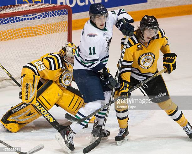 Connor Chatham of the Plymouth Whalers battles out front of the net against Joshua Chapman and Taylor Dupuis of the Sarnia Sting on February 21 2014...