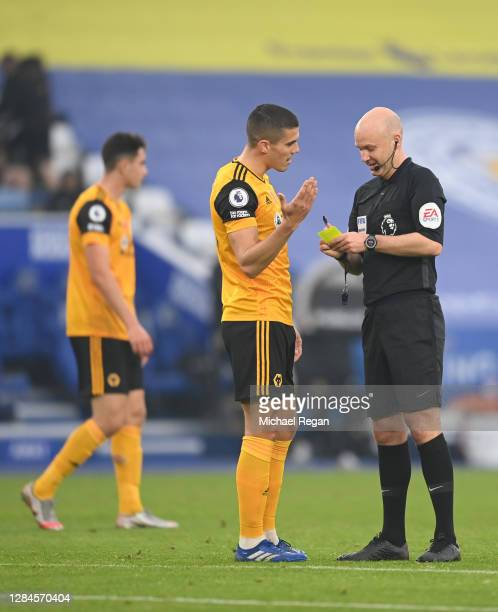 Connor Coady of Wolverhampton Wanderers speaks to referee Anthony Taylor after being booked during the Premier League match between Leicester City...