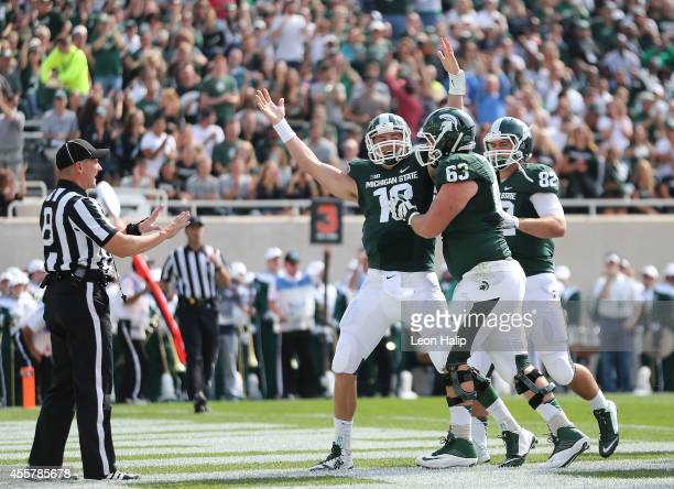 Connor Cook of the Michigan State Spartans celebrates after scoring on a 4-yard run during the first quarter of the game against Eastern Michigan...