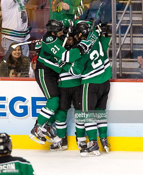 Connor Gaarder of North Dakota celebrates his goal against the Minnesota Golden Gophers with teammates Jordan Schmaltz and Brendan O'Donnell during...