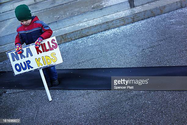 Connor Garrett holds a sign during a rally at the Connecticut State Capital to promote gun control legislation in the wake of the December 14 school...