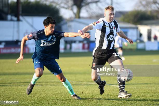 Connor Hall of Chorley FC is challenged by Harrison Solomon of Derby County during the FA Cup Third Round match between Chorley and Derby County at...