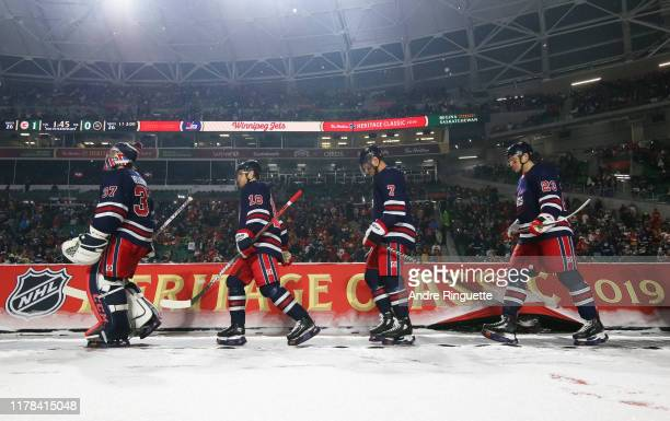 Connor Hellebuyck Bryan Little Dmitry Kulikov and Carl Dahlstrom of the Winnipeg Jets walk to the ice for the third period against the Calgary Flames...
