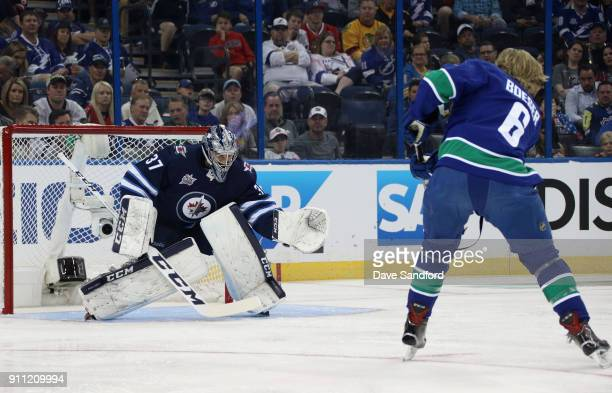 Connor Hellebuyck of the Winnipeg Jets and Brock Boeser of the Vancouver Canucks compete in the GEICO NHL Save Streak during 2018 GEICO NHL AllStar...