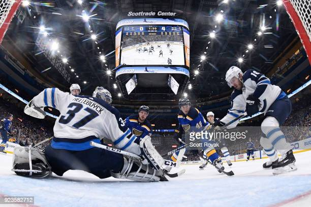 Connor Hellebuyck of the Winnipeg Jets and Bryan Little of the Winnipeg Jets defend against Vladimir Sobotka of the St Louis Blues and Ivan Barbashev...