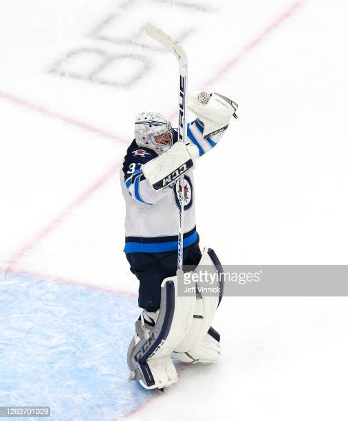 Connor Hellebuyck of the Winnipeg Jets celebrates the win over the Calgary Flames during Game Two of the Western Conference Qualification Round prior...