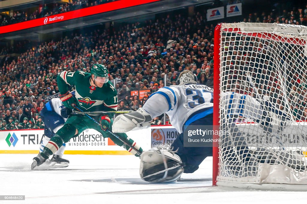 Connor Hellebuyck #37 of the Winnipeg Jets defends against Marcus Foligno #17 of the Minnesota Wild during the game at the Xcel Energy Center on January 13, 2018 in St. Paul, Minnesota.