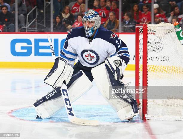 Connor Hellebuyck of the Winnipeg Jets defends his net against the New Jersey Devils during the game at Prudential Center on March 28 2017 in Newark...