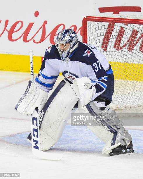 Connor Hellebuyck of the Winnipeg Jets in action against the Calgary Flames during an NHL game at Scotiabank Saddledome on October 7 2017 in Calgary...