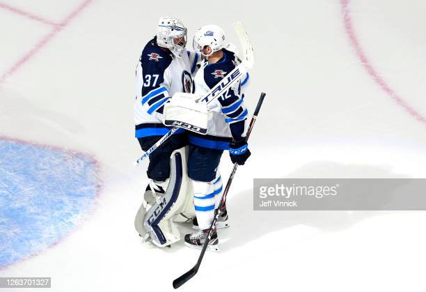 Connor Hellebuyck of the Winnipeg Jets is congratulated by teammate Dylan DeMelo after the win over the Calgary Flames in Game Two of the Western...