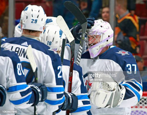 Connor Hellebuyck of the Winnipeg Jets is congratulated by teammates Bryan Little and Patrik Laine after winning their NHL game against the Vancouver...