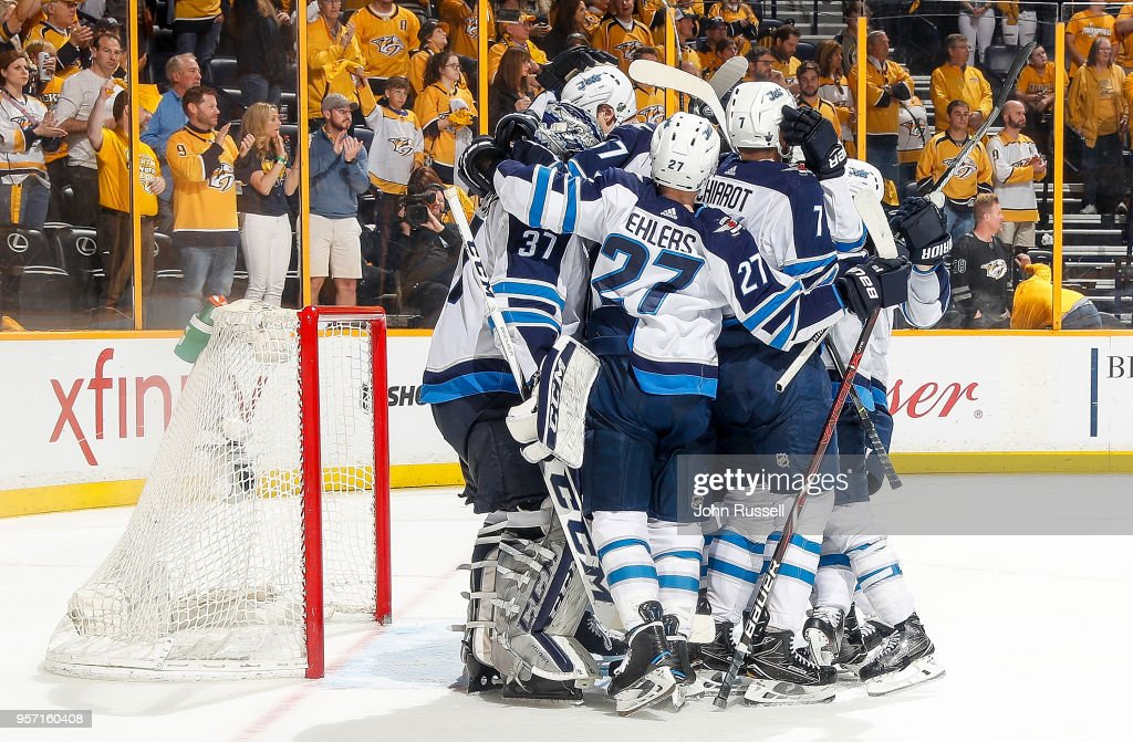 Connor Hellebuyck #37 of the Winnipeg Jets is congratulated by teammates after a 5-1 win in Game Seven of the Western Conference Second Round during the 2018 NHL Stanley Cup Playoffs at Bridgestone Arena on May 10, 2018 in Nashville, Tennessee.