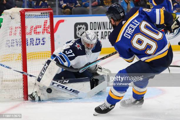 Connor Hellebuyck of the Winnipeg Jets makes a save against Ryan OReilly of the St. Louis Blues at the Enterprise Center on February 6, 2020 in St....