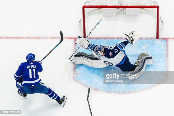Connor Hellebuyck of the Winnipeg Jets makes a save against the Zach Hyman of the Toronto Maple Leafs during the third period at the Scotiabank Arena...