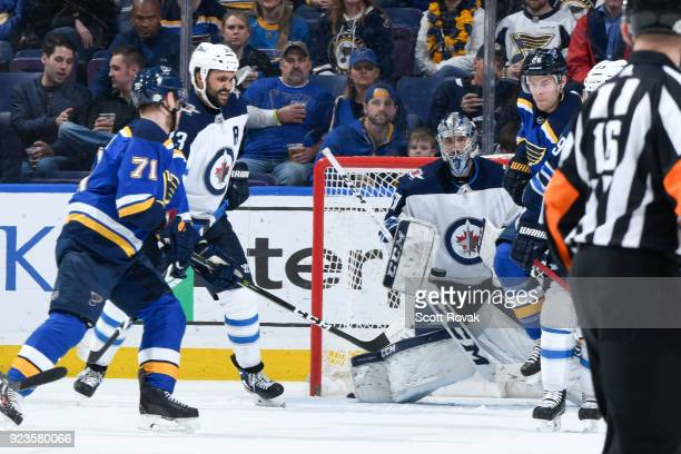 Connor Hellebuyck of the Winnipeg Jets makes a save as Dustin Byfuglien of the Winnipeg Jets defends against Vladimir Sobotka of the St Louis Blues...