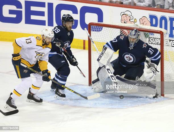 Connor Hellebuyck of the Winnipeg Jets makes a save off Nick Bonino of the Nashville Predators in Game Six of the Western Conference Second Round...
