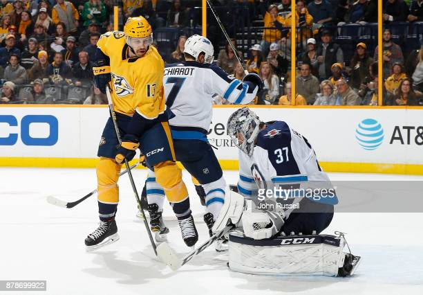 Connor Hellebuyck of the Winnipeg Jets makes the save against Nick Bonino of the Nashville Predators during an NHL game at Bridgestone Arena on...