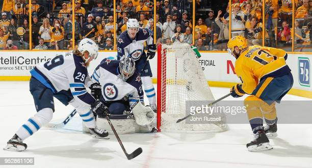 Connor Hellebuyck of the Winnipeg Jets makes the save against Nick Bonino of the Nashville Predators as Patrik Laine defends in Game Two of the...
