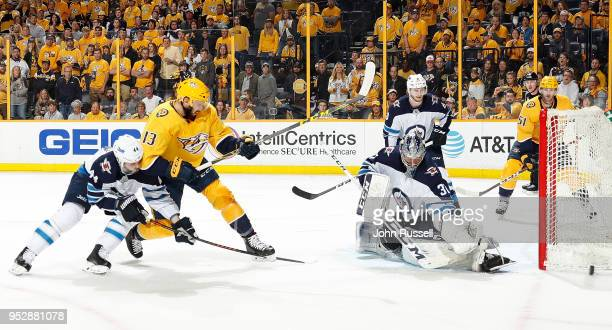 Connor Hellebuyck of the Winnipeg Jets makes the save against Nick Bonino of the Nashville Predators as Josh Morrissey defends in Game Two of the...