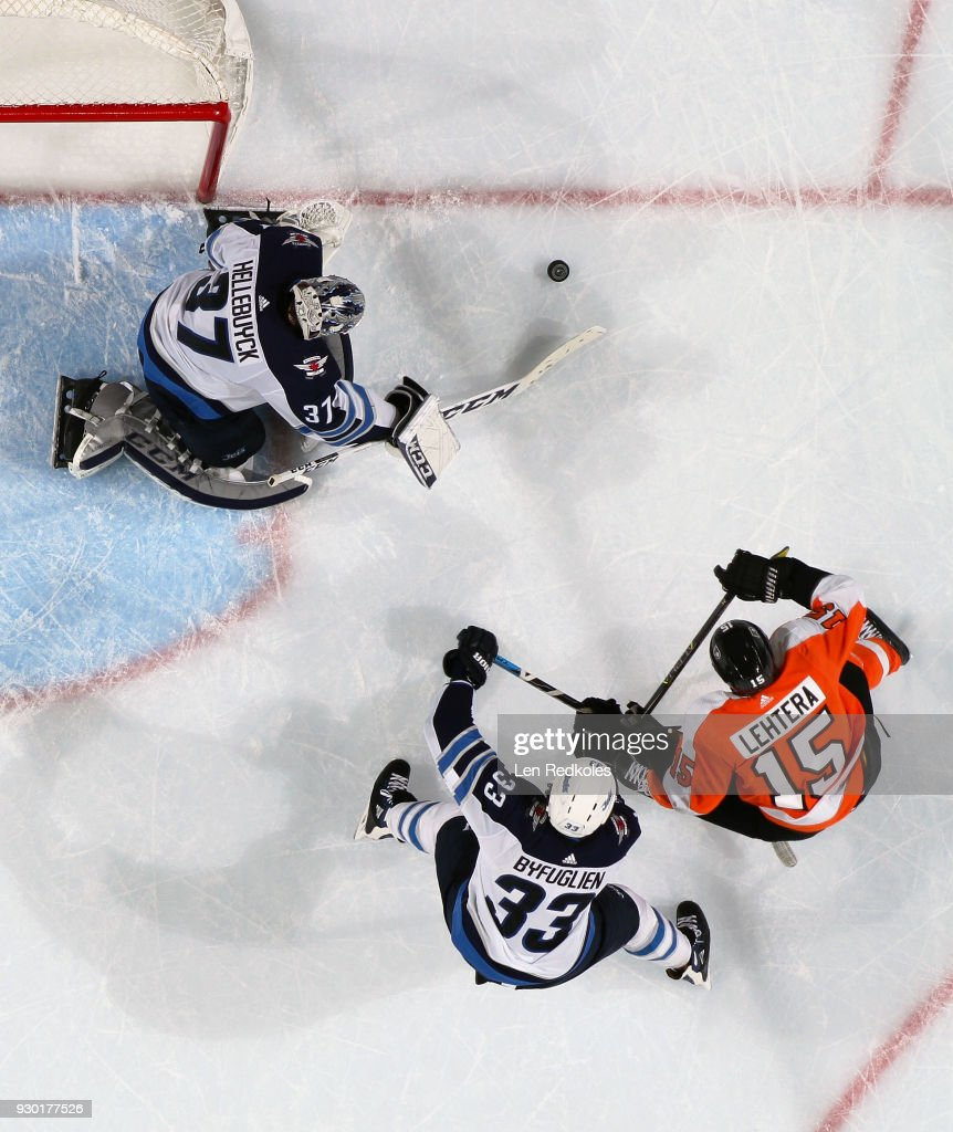 Connor Hellebuyck #37 of the Winnipeg Jets plays the loose puck away from his net while Dustin Byfuglien #33 defends against Jori Lehtera #15 of the Philadelpia Flyers on March 10, 2018 at the Wells Fargo Center in Philadelphia, Pennsylvania. The Flyers went on to defeat the Jets 2-1.