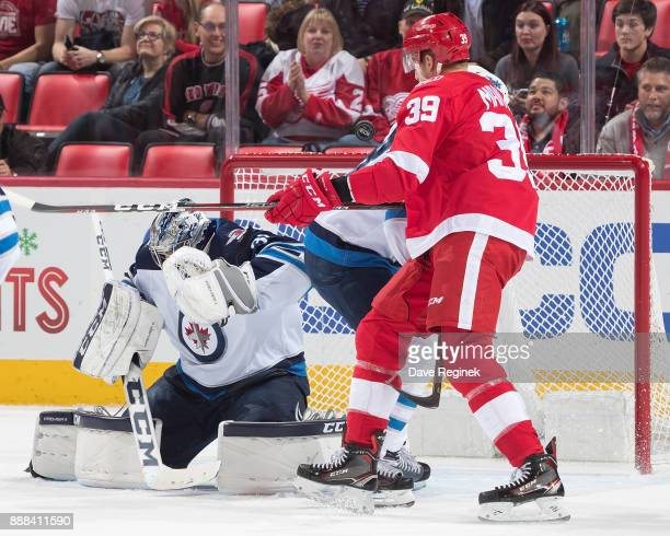 Connor Hellebuyck of the Winnipeg Jets reacts on a shot as Anthony Mantha of the Detroit Red Wings looks for the rebound during an NHL game at Little...