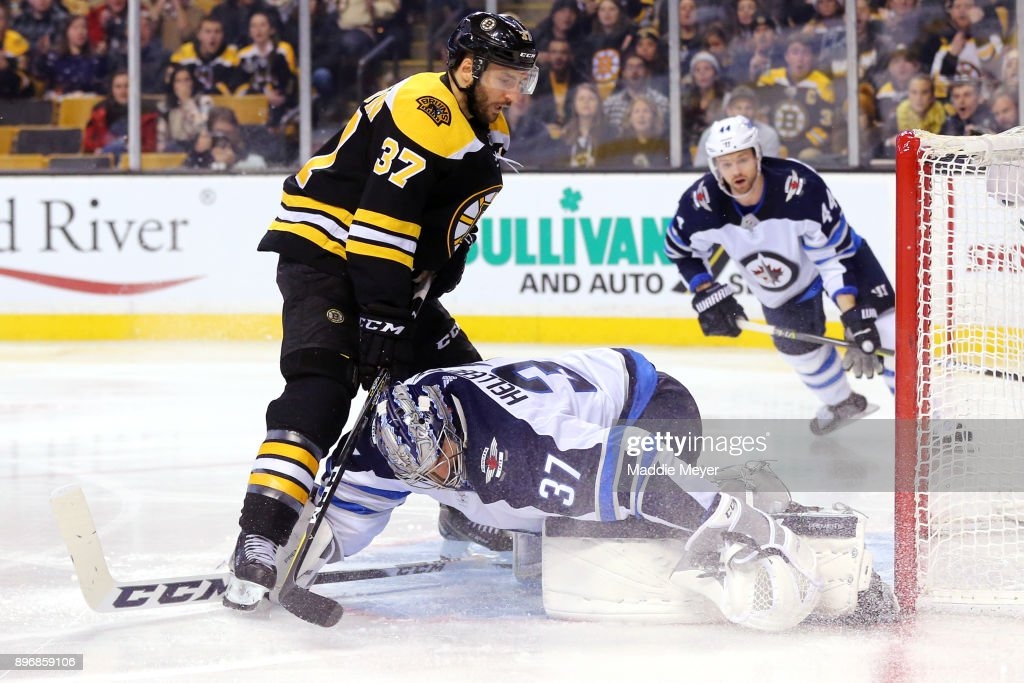Connor Hellebuyck #37 of the Winnipeg Jets saves a shot from Patrice Bergeron #37 of the Boston Bruins during the third period at TD Garden on December 21, 2017 in Boston, Massachusetts. The Bruins defeat the Jets 2-1 in a shoot out.
