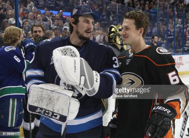 Connor Hellebuyck of the Winnipeg Jets talks with Rickard Rakell of the Anaheim Ducks during 2018 GEICO NHL AllStar Skills Competition at Amalie...