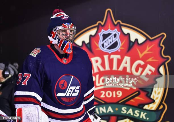 Connor Hellebuyck of the Winnipeg Jets walks to the ice to start the third period against the Calgary Flames during the 2019 Tim Hortons NHL Heritage...