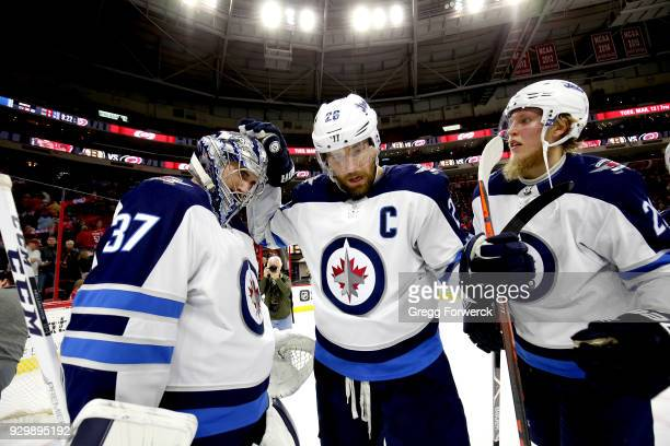 Connor Hellybuyck of the Winnipeg Jets is congratulated by teammates Blake Wheeler and Patrik Laine following a victory over the Carolina Hurricanes...
