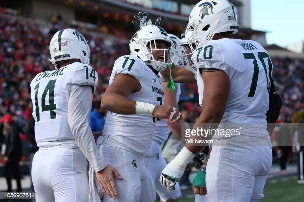 Connor Heyward of the Michigan State Spartans celebrates with Tyler Higby and Brian Lewerke of the Michigan State Spartans after scoring a touchdown...