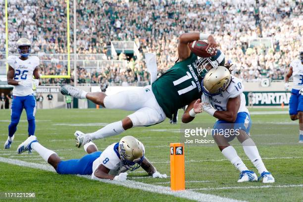 Connor Heyward of the Michigan State Spartans dives toward the end zone pylon for a 15-yard touchdown in the first quarter against Manny Bunch of the...