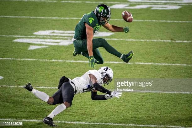 Connor Heyward of the Michigan State Spartans loses control of the ball as he leaps over A.J. Hampton of the Northwestern Wildcats during the fourth...