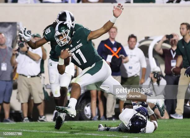 Connor Heyward of the Michigan State Spartans scores a fourth quarter touchdown past the tackle of Dj Williams of the Utah State Aggies at Spartan...