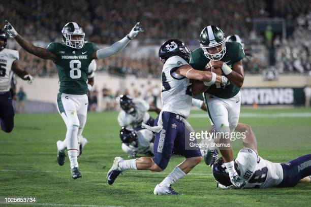 Connor Heyward of the Michigan State Spartans scores a third quarter touchdown past Gaje Ferguson of the Utah State Aggies at Spartan Stadium on...