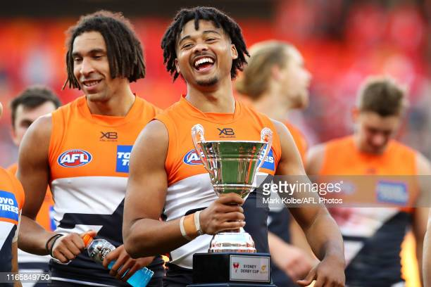 Connor Idun of the Giants shares a laugh with his team mates as he leaves the field holding the Sydney Derby Cup after victory during the round 20...