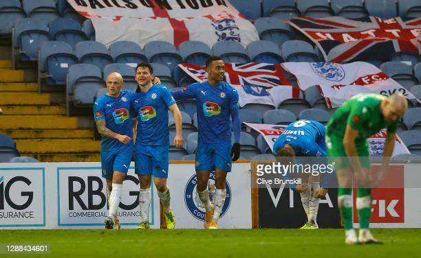 Connor Jennings of Stockport County celebrates with team mates Alex Reid and Sam Minihan after scoring their sides third goal during the Emirates FA...