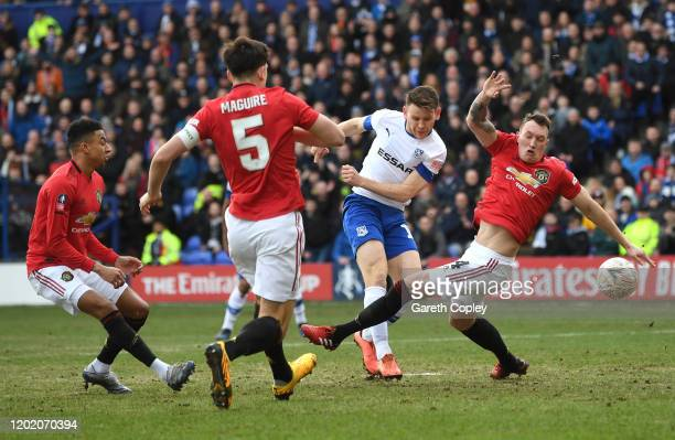 Connor Jennings of Tranmere Rovers shoots past Phil Jones of Manchester United during the FA Cup Fourth Round match between Tranmere Rovers and...