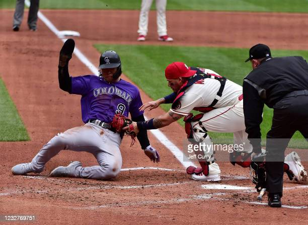 Connor Joe of the Colorado Rockies is tagged out at home by Yadier Molina of the St. Louis Cardinals during the second inning at Busch Stadium on May...